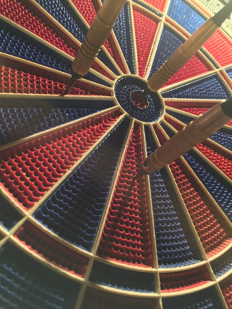A blue and red target with 3 darts on it.