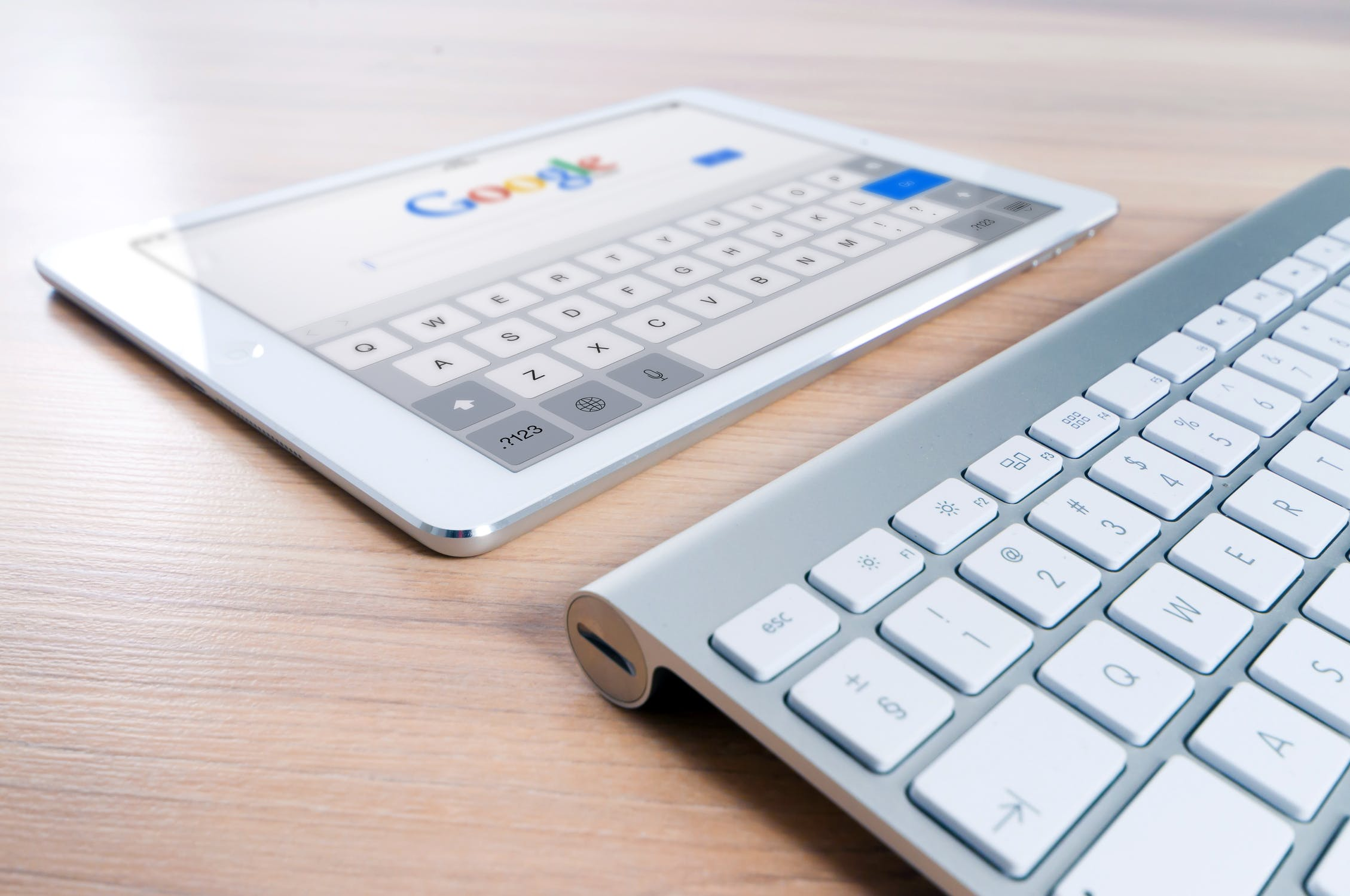 A silver iPad on a wooden surface, showing Google's search engine page.