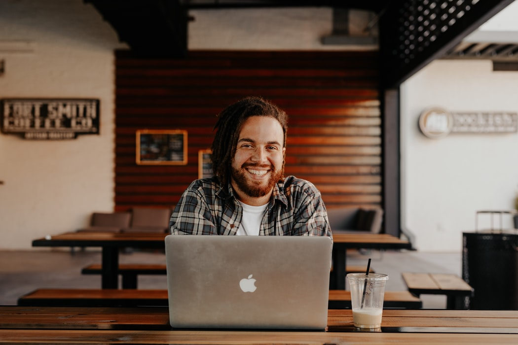Smiling man sitting in front of a laptop.
